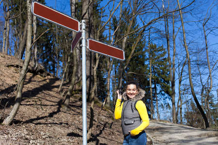 where to go: Pretty sporty girl standing at crossroads, under signpost, waypost and trying to decide where to go, space for text, Choice concept