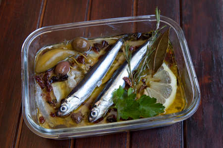 Sardines carpaccio fillets, tasty decorated in glass dish, with Mediterranean organic herbs, rosemary, laurel, capers, olives and covered with extra virgin olive oil, closeup, selected focus photo