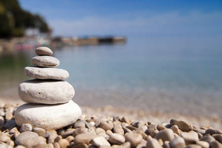 Stack of stones on sandy sea beach against dramatic background, Zen, Feng shui concept, selective focus Stock Photo