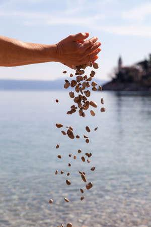 Notion symbolique de la paix, le pardon, le pardon, la miséricorde, la compassion, Mains tomber beaucoup de pierres dans la mer. Mise au point sélective, contre la mer bleue et le ciel