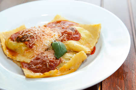 Delicius italian pasta, Ravioli on white plate, for stuffing is used organic vegetables, decorated with tomato sauce, fresh Mediterranean basil and parmesan, Parma cheese, selective focus, close up photo