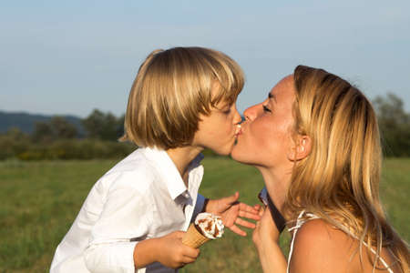 Young boy with icecream  kissing his cute mother on sunny summer day