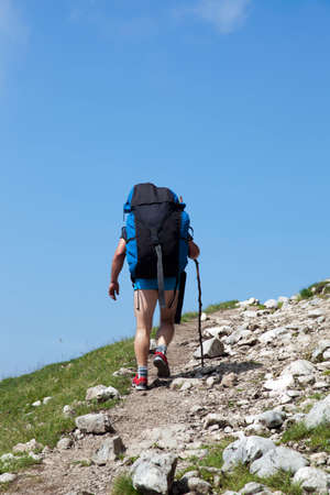 high flier: Paraglider,  trekker, mountaineer, walking up hill to a paragliding starting point, on a sunny morning, high in the mountains, space for text