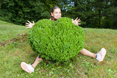boxwood: Pretty young woman hugging the boxwood