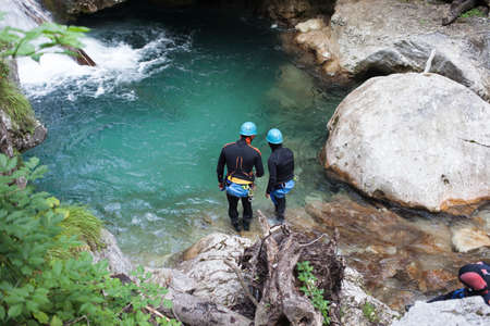 diving save: A river search and rescue team on duty in river pool under waterfall in National park, Tscheppaschlucht, Austria Stock Photo