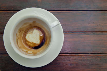 Cup of coffee with Heart of Coffee Grounds, on wooden table, fortunetelling, divination symbol of love Standard-Bild