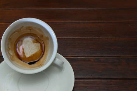 fortunetelling: Cup of coffee with Heart of Coffee Grounds, on wooden table, fortunetelling, divination symbol of love Stock Photo