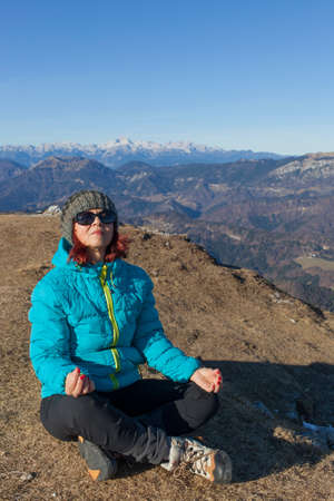 joga: Pretty mid aged woman trekker relaxing, performing JOGA high in mountains on sunny winter day against  Mount Triglav, highest mountain in Slovenian  Alps, space for text Stock Photo