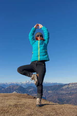 Pretty mid aged woman trekker relaxing, performing JOGA high in mountains on sunny winter day against  Mount Triglav, highest mountain in Slovenian  Alps, space for text Stock Photo
