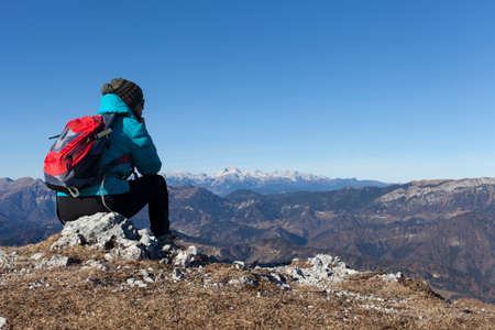 open country: Pretty mid aged woman trekker with backpack resting high in mountains on sunny winter day whilst watching Mount Triglav, highest mountain in Slovenian  Alps, space for text Stock Photo