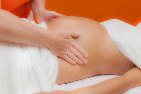 therapeutic massage: Pregnant young latina woman with beautiful skin, being wrapped with a towel, lying on a bed and having a relaxing prenatal massage, various techniques, glamour clarity effect