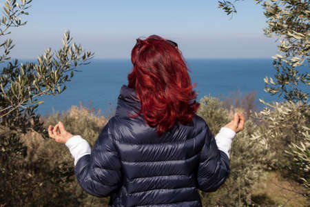 joga: Pretty middle aged woman with red hair meditating, performing joga in beautiful organic olive grove above the sea coast on windy sunny day Stock Photo