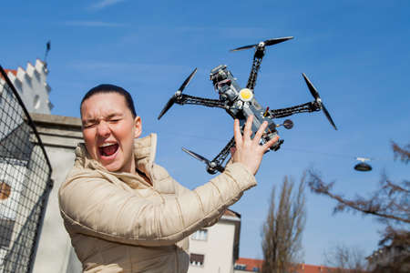 Pretty young woman screams just a moment before drone quadrocopter attack or hit, in the city, on sunny day, space for text