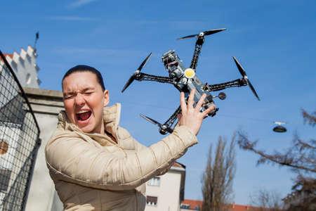 Mooie jonge vrouw schreeuwt net even voor drone quadrocopter aanval of raakte, in de stad, op een zonnige dag, ruimte voor tekst Stockfoto