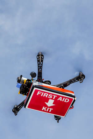 navigation aid: UAV drone quadrocopter with modern GPS navigation transporting First aid kit crate, against blue sky, space for text Stock Photo