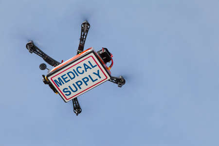 UAV drone quadrocopter with modern GPS navigation transporting box with medical supplies, against blue sky, space for text