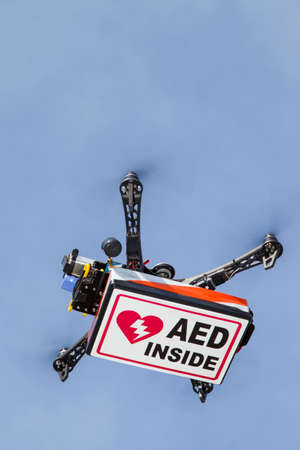 defibrillator: UAV drone quadrocopter with modern GPS navigation transporting Automated external defibrillator AED, against blue sky, space for text