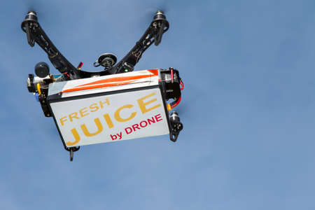 UAV drone quadrocopter with modern GPS navigation transporting fresh juice in the box, against blue sky, space for text