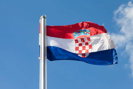 metal pole: Croatian flag on a metal pole, fluttering in strong bora north-east wind, Sinj fortress, against blue sky, space for text Stock Photo