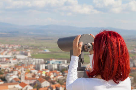 Sinj, Croatia, Woman with red hair looking through a coin operated binoculars, rear view