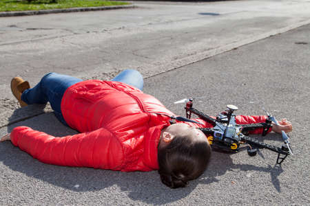 Pretty woman attacked by drone quadrocopter with bleeding head injuries,  lying on sidewalk in the city