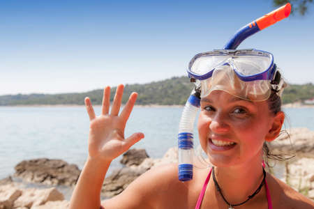 diving mask: Lovely suntanned smiling girl at the seaside wearing a diving mask and waving hello, space for text