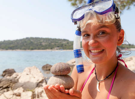diving mask: Lovely smiling girl at the seaside wearing a diving mask and holding sea urchins skeletons, space for text