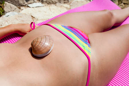 suntanned: Suntanned  attractive girl in colorful bikini is lying on a sunny beach with a seashell on her belly, close-up Stock Photo