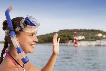 suntanned: Lovely suntanned smiling girl at the seaside wearing a diving mask and waving hello, space for text