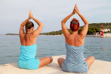 joga: Mother and daughter performing joga on beach, sea coast, meditating in yoga pose on sunny summer day