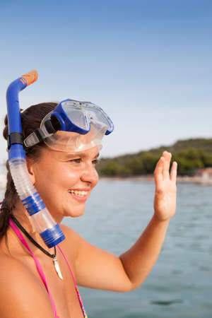 suntanned: Lovely suntanned smiling girl at the seaside waving hello, space for text