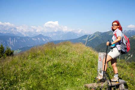salto de valla: Salto feliz de la mujer de caminante sobre la cerca eléctrica, rojo marca de camino de montaña, alto en la montaña, el espacio para el texto