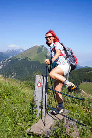 salto de valla: Happy woman hiker jumping over electric fence, red mountain trail mark, high in the mountain, space for text