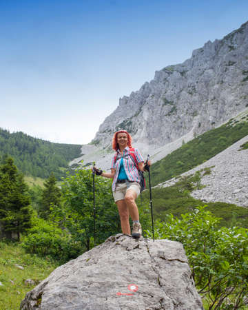 age forty: Mid-aged  woman hiker resting on  big rock with red signpost, on the way to high mountain in  Alps