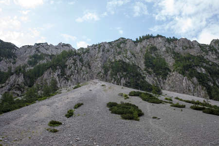 to incline: Scree is a slope of loose rock debris at the base of a steep incline or cliff, beautiful calm cloudy morning in Slovenian  Alps, Europe
