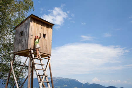 Pretty mid aged woman trekker sitting on hunters high tower, wooden hunters high seat in the mountain forest, against blue sky Stock Photo