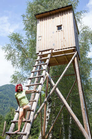 hunters tower: Pretty mid aged woman trekker sitting on hunters high tower, wooden hunters high seat in the mountain forest, against blue sky Stock Photo