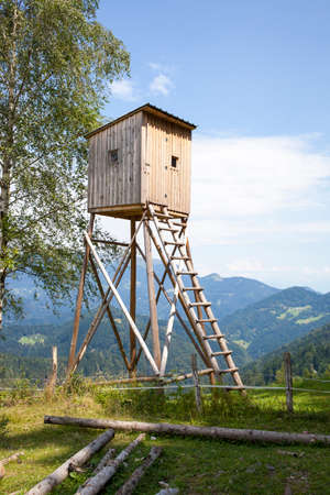 Hunters high tower. Wooden hunters high seat in the mountain forest, against blue sky
