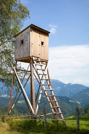 hunter's cabin: Hunters high tower. Wooden hunters high seat in the mountain forest, against blue sky