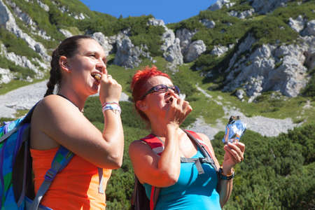 chocolate peak: Mother and daughter eating sport power muesli bar, enjoying granola cereal bars, living healthy active lifestyle in mountain nature