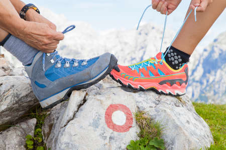 trail sign: Two hikers tying boot laces on rock with red trail sign, high in the mountains, space for text Stock Photo