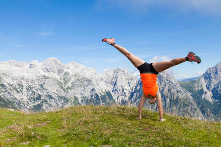 joyfully: Young pretty women joyfully jumping and performing cartwheel, outdoors high in the mountains, on sunny summer day