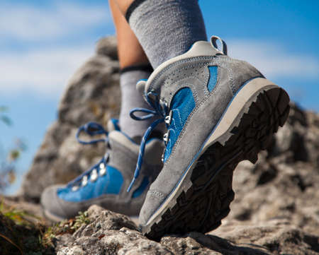 Close up of hiking boots and legs climbing up rocky trail and reaching the top of a mountain Standard-Bild