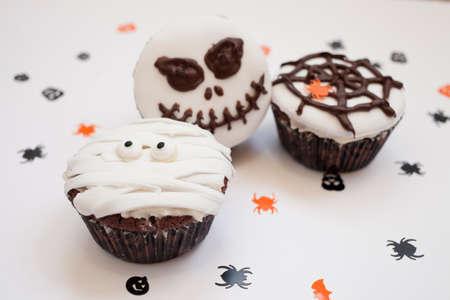 El hogar hizo las magdalenas muffins de Halloween espeluznante y escalofriante como momias, red de la araña y el horror de calabaza, decorada con chocolate para la fiesta de Halloween, en el fondo de color blanco brillante, atención selectiva