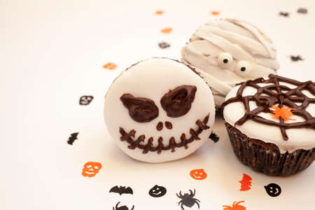 Home made Halloween spooky and creepy muffin cupcakes as a mummies, spider net and horror pumpkin, decorated with chocolate to Halloween party, on bright white background, selective focus Stock Photo