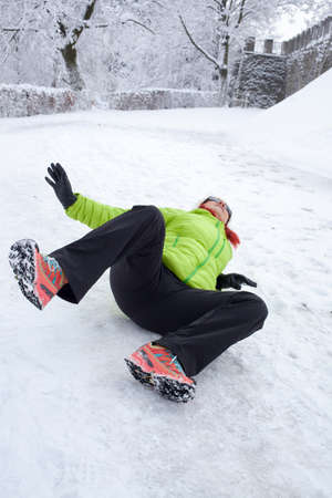 Risk of accidents in winter. Mid aged woman is slipping and falling on footpath, street covered with snow and black ice Stock Photo