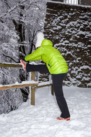 Sport  mid aged woman doing stretching fitness exercise in winter city park forest