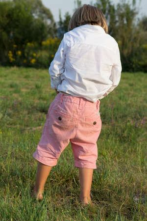 Young blonde boy peeing outdoors on green grass, on sunny summer afternoon Stock Photo