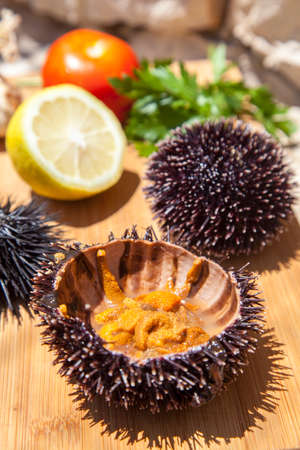 Fresh Sea Urchin served with mediterranean lemon, tomatoes, garlic, parsley, on wooden plate in stone house exterior Stock Photo