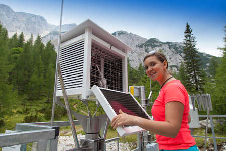 hygrometer: Smiling pretty woman meteorologist reading meteodata instruments in modern meteorologic observation station, high in mountains Stock Photo